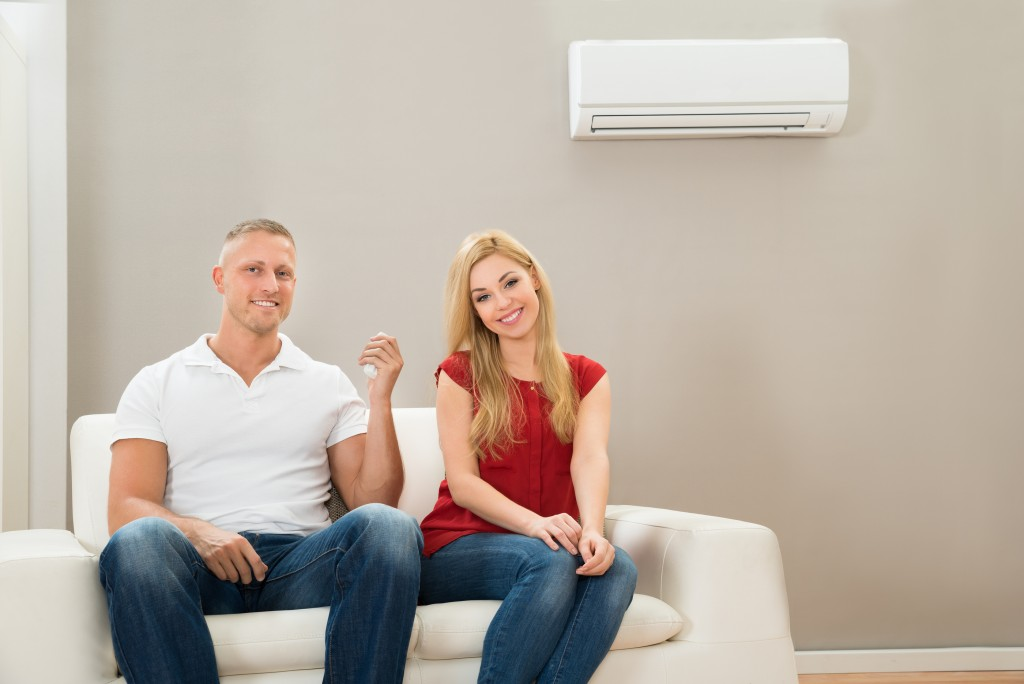 Young Happy Couple Sitting On Sofa Using Air Conditioner